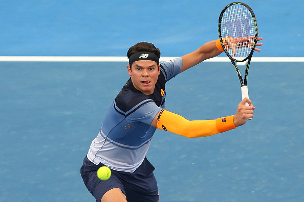Milos Raonic plays a backhand volley in his New Balance outfit during his semi-final match at the Brisbane international.